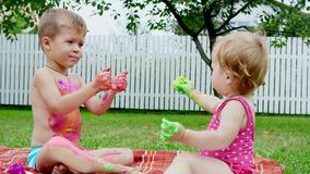 Small children, a four-year-old boy and a one-year-old girl, brother and sister, play together, paint with finger paints stock video footage