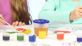 Small children with the help of brushes and paints decorate drawings, they like it. Close up. White background. Two little girls sit at the table and decorate stock footage