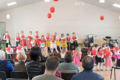 Small children in kindergarten dance on stage in front of their parents. Mom removing the performance of children on the royalty free stock photos