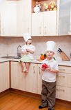 Small children on kitchen Stock Image