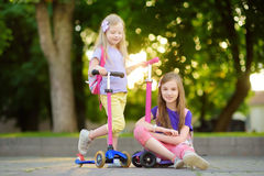 Small children learning to ride scooters in a city park on sunny summer evening. Cute little girls riding rollers. Active leisure and outdoor sport for kids Stock Photo