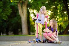 Small children learning to ride scooters in a city park on sunny summer evening. Cute little girls riding rollers. Active leisure and outdoor sport for kids Stock Image