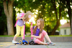 Small children learning to ride scooters in a city park on sunny summer evening. Cute little girls riding rollers. Active leisure and outdoor sport for kids Royalty Free Stock Image
