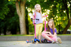 Small children learning to ride scooters in a city park on sunny summer evening. Cute little girls riding rollers. Active leisure and outdoor sport for kids Stock Images