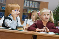 Small children at a lesson. Boys and girls at a lesson at school sit at school desks Royalty Free Stock Image