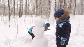 Small children make a snowman in winter Park. Winter holidays stock footage