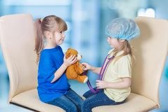 Small children playing a doctor and a pediatrician touching a toy bear with a stethoscope stock photos