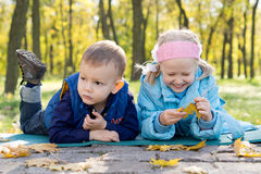 Small Children Relaxing in a Park in Autumn Royalty Free Stock Image