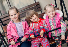 Small children ride on a wooden swing Stock Photo