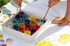 Small children`s hands paint with paints and brushes on a large sheet on the street on a Sunny day, creativity and fun royalty free stock image