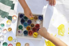Small children`s hands paint with paints and brushes on a large sheet in the street on a Sunny day, creativity and fun, the top po