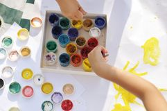 Small children`s hands paint with paints and brushes on a large sheet in the street on a Sunny day, creativity and fun, the top po stock photos