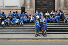 Small children from school sitting on the steps of the entrance to the Lima Cathedral in Peru. Royalty Free Stock Photo