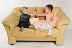 Small children sitting on the sofa with a gift box. The boy gives a girl a heart-shaped lollipop royalty free stock images