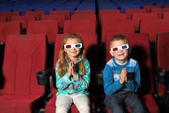 Small children smiling in 3D glasses and clapping Royalty Free Stock Photo
