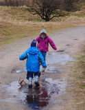 Small children  splashing in a muddy puddle Royalty Free Stock Photo