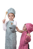 Small children, with a wooden spoon and cook costume Royalty Free Stock Photo