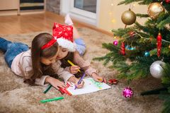 Two little sisters write the letter to Santa under the Christmas tree stock images