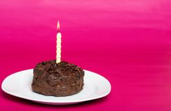 Small chocolate cake with birthday candle Royalty Free Stock Photo