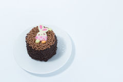 Small chocolate cake with Easter bunny detail on a white dish is Royalty Free Stock Photography