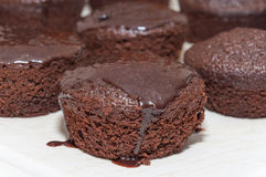 Small chocolate cakes with dripping chocolate icing on top Stock Photos