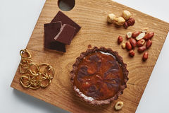 Small Chocolate Tart with huzelnuts and peanut on a white background Stock Images