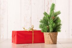 Small chrismast tree and gift on wooden background