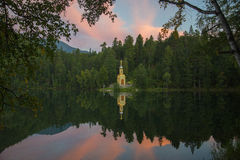 A small Christian chapel stands on the shore of forest lake. Stock Photography