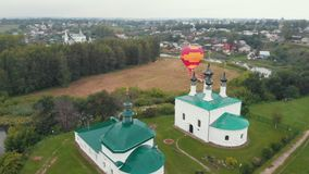 Small christian village - air balloon festival - a balloon about to take off in the sky - Suzdal, Russia. Aerial view stock video footage