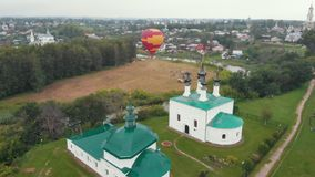 Small christian village - a balloon flying in the sky - Suzdal, Russia. Aerial view stock footage