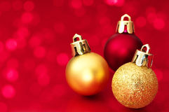 Small Christmas balls on red sparkle background. Royalty Free Stock Photo