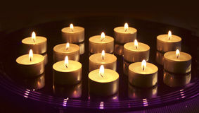 Small Christmas candles. Burning on glass tray, on dark background royalty free stock image