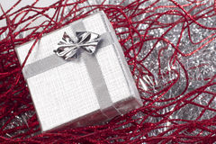 Small christmas gift in red christmas decorations. Small silver gift in red christmas decorations Royalty Free Stock Photos