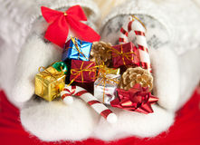 Small christmas gifts in palms of hands Royalty Free Stock Photos
