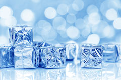 Small Christmas gifts in shiny paper, blue bokeh lights Stock Photo