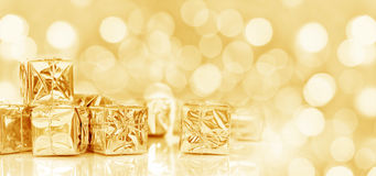 Small Christmas gifts in shiny paper, panoramic christmas golden background Royalty Free Stock Photos