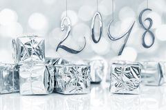 2018, small Christmas gifts in shiny silver paper, bokeh lights Royalty Free Stock Photo
