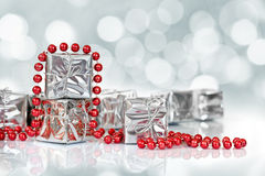 Small Christmas gifts in shiny silver paper and red tinsel beads. Ornament Stock Image