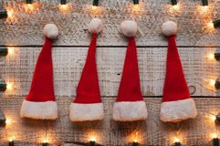 Small christmas hats on old wooden table with xmas lights frame. Holidays season accessories royalty free stock photography