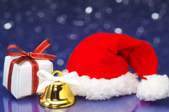 Small Christmas present and Santa hat on white sparkle backgroun Royalty Free Stock Image