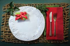Small Christmas present tied with a bright red bow on handmade white plate with holly and red linen napkin. Horizontal aspect Stock Photos