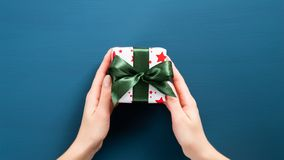 Free Small Christmas Present With Green Ribbon Bow In Woman Hands. Female Hands Holding Gift Box Wrapped Festive White Paper Over Dark Stock Image - 162833901