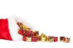 Small christmas presents falling from santas hat Stock Photography