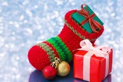 Small Christmas stocking and presents on white sparkle backgroun Stock Photos
