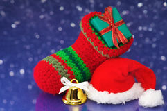 Small Christmas stocking and Santa hat on white sparkle backgrou Royalty Free Stock Image