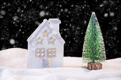 Small Christmas toy house and fir tree on snowing night stock photo