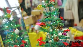 Small Christmas tree with bright garlands creating holiday atmosphere in store. Stock footage stock video footage