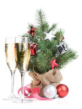 Small christmas tree with decor and two champagne glasses Royalty Free Stock Photos