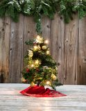 Small Christmas tree decoration on rustic wood with snowy backgr Stock Image