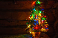Small Christmas tree with multi colored lights at dark countryside room Royalty Free Stock Photography